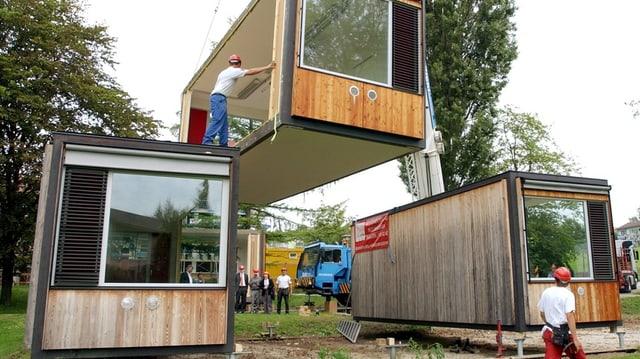 Mehrere Arbeiter platzieren mit eine Krank Pavillons für die Schule.