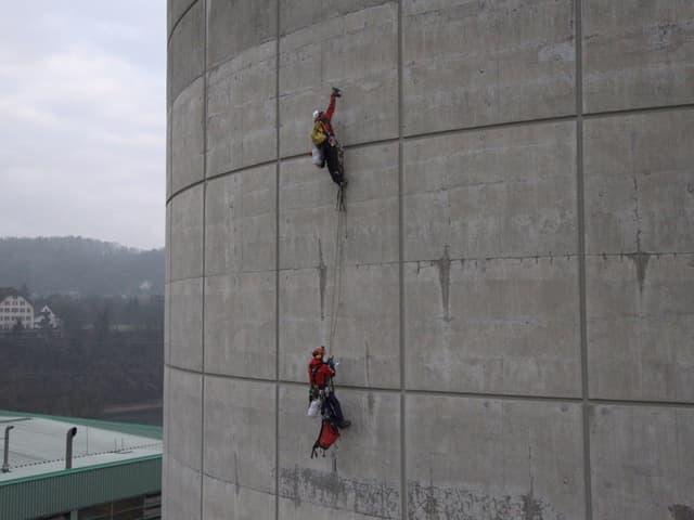 Aktivisten hängen mit Seilen an der Kühlturmwand