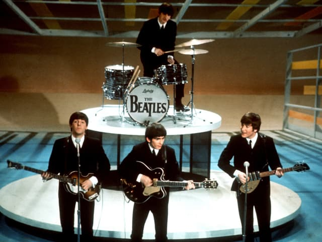 Vier junge Männer im Anzug auf einer Bühne, spielen Gitarre und Schlagzeug.