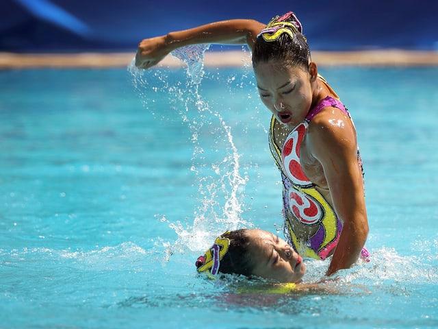 Schwimmerin mit geballter Faust über der zweiten.