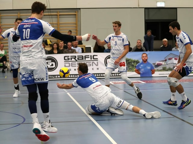 Volleyball-Spieler hechtet dem Ball nach.