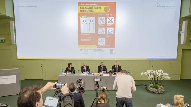 Vier Personen sitzen vor einer Leinwand mit Warnhinweisen.
