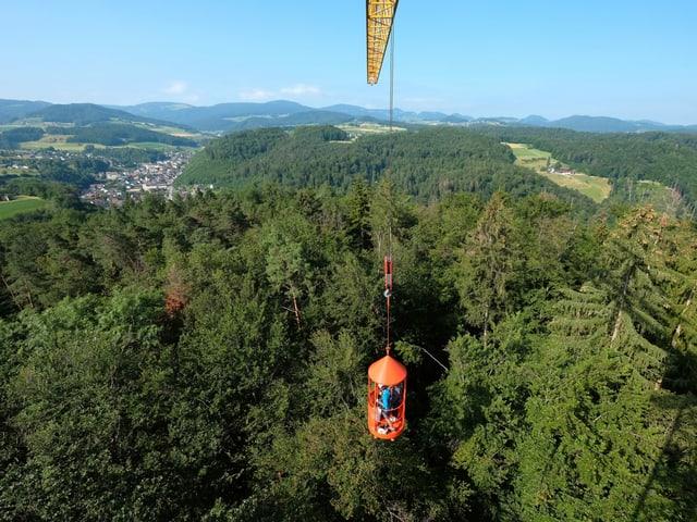 Rote Kabine schwebt über den Bäumen.