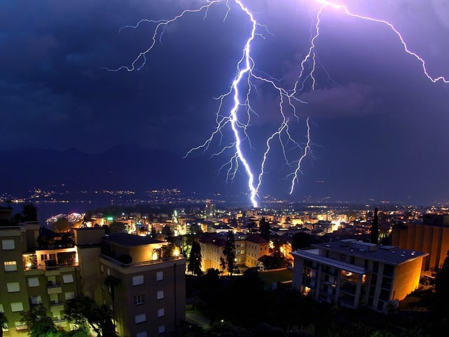 Die Lichter der Stadt Locarno leuchten. Ein greller Blitz schlägt in Ufernähe ein.