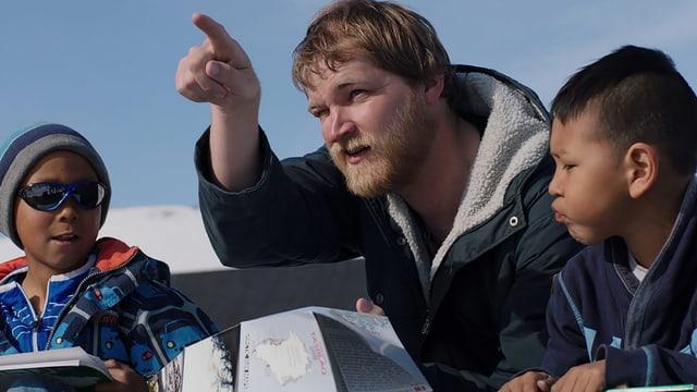 Der dänische Lehrer erklärt seinen grönländischen Schülern etwas.