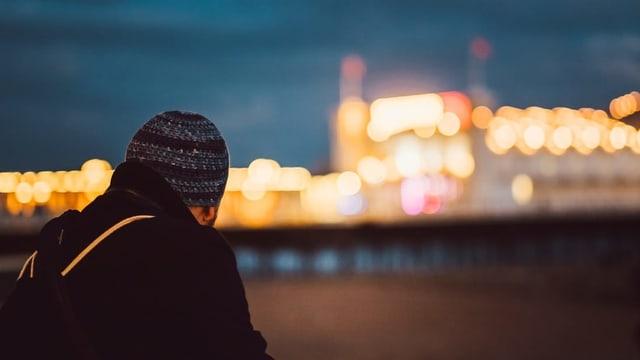 Ein junger Mann mit Kappe schaut aus der Ferne auf eine beleuchtete Stadt.