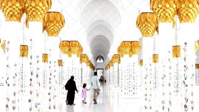 Ein Mann, eine Frau in Tschador und ein Kind laufen durch einen Gang in der Moschee.