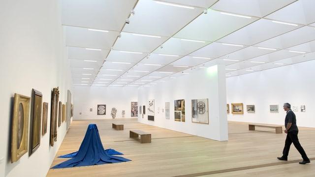 Ein Mann geht durch helle Ausstellungsräume mit Kunstwerken an den Wänden und am Boden
