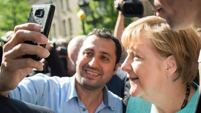 Merkel beim Selfie mit einem Flüchtling.