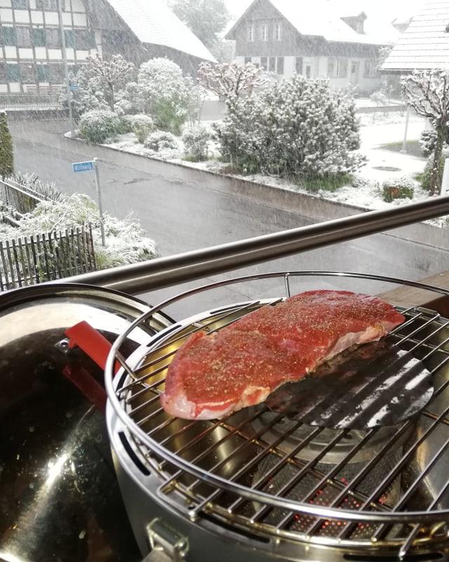 Balkonszene. Steak auf Grill. Dahinter sieht man, wie es schneit.