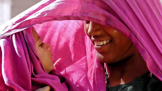 Ina mamma en l'India protegia ses uffant dal sulegl.