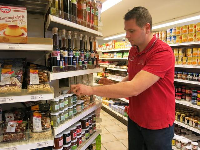 Ein Mann steht vor einem Lebensmittelregal.