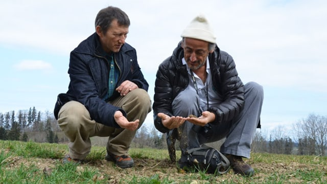 Rampini und Diaz knieen am rande eines Ackers und schauen die Bodenbeschaffenheit an.