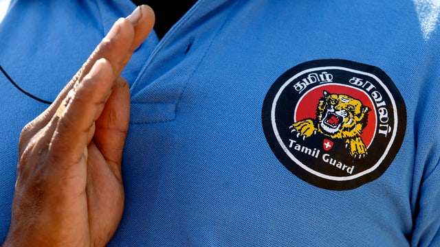 In um cun in logo da la Tamil Guard.