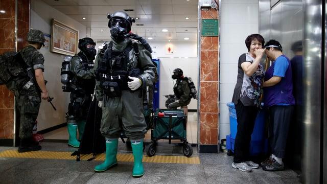 Südkoreanische Polizisten in Schutzanzügen.