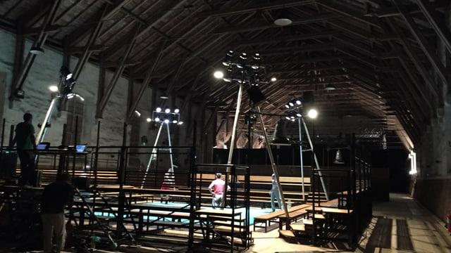 Das Innere der Reithalle Aarau mit Sitzbänken und Scheinwerfern.