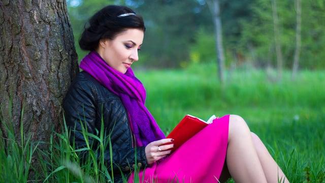 Eine Frau liest an einen Baum gelehnt ein Buch