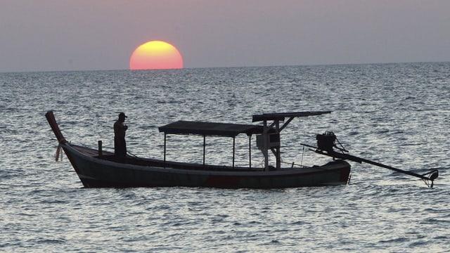 Ein Fischerboot vor der untergehenden Sonne.