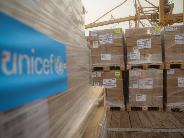 Palletten mit Kartons auf einem Schiff, Hilfslieferung mit Unicef angeschrieben
