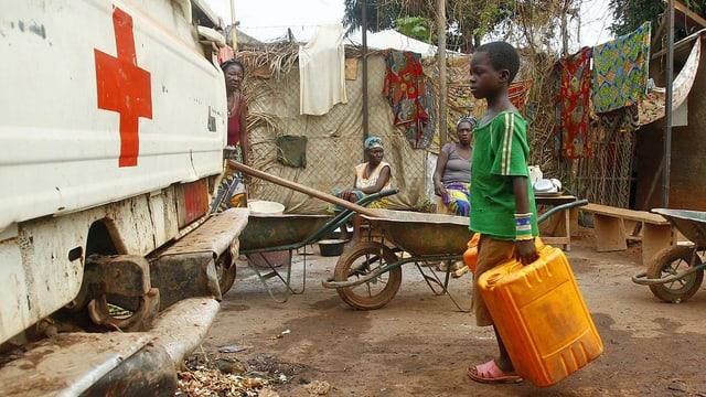 Kind wartet mit Wasserkanister.