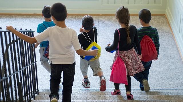 Kinder mit bunten Schultaschen laufen eine Treppe hinunter.