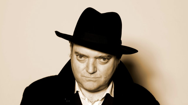 Porträtaufnahme von Wiglaf Droste. Er trägt einen schwarzen Mantel, weisses Hemd und einen schwarzen Hut.