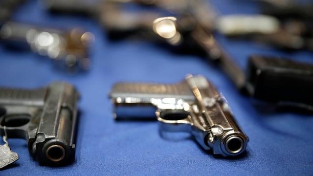 Verschiedene Schusswaffen auf einer blauen Unterlage.