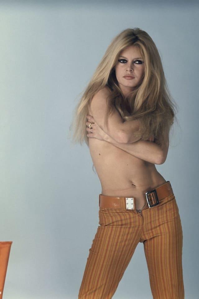 Brigitte Bardot oben ohne mit Armen verschränkt bei einem Fotoshooting.