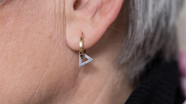 Nahaufnahme eines Ohrs: An einem Ohrring hängt ein Dreieck.