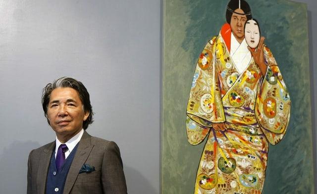 ein Mann in Anzug steht vor einem Gemälde