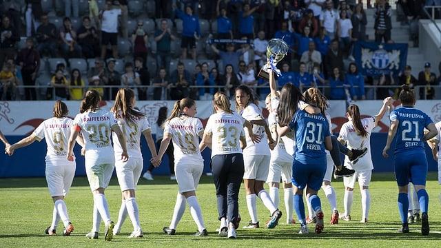 Spielerinnen des FCZ feiern vor Zuschauern im Stadion.