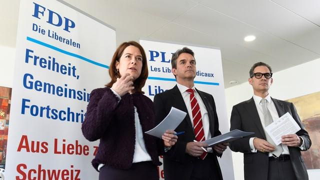 Frau und zwei Männer vor Plakaten mit Slogans der FDP.