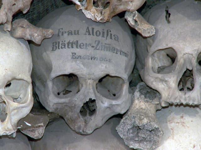 Totenköpfe im Beinhaus von Stans, einer beschrieben mit dem Namen der Verstorbenen.