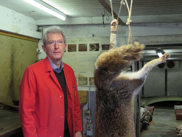 Ein Mann steht neben einem toten aufgehängten Fuchs