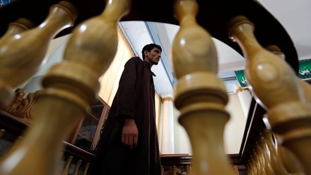 Ein Afghane in einem Gerichtssaal, fotografiert durch ein Treppengeländer hindurch.