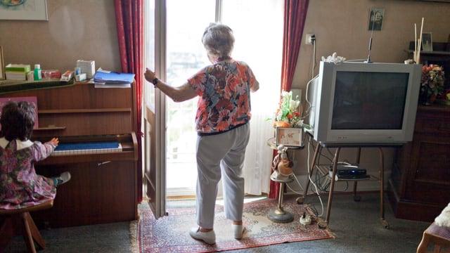Ein ältere Frau öffnet das Fenster zu ihrer Terrasse