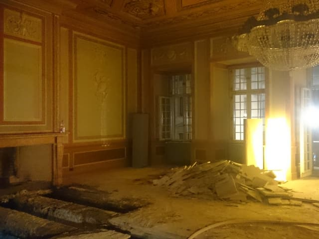 Ein Raum mit Kronleuchter und stark beschädigtem Boden des historischen Gebäudes.
