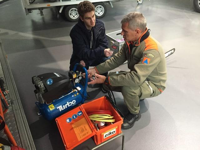 Zwei Männer knien am Boden vor technischem Gerät, einer mit Mikrofon in der Hand