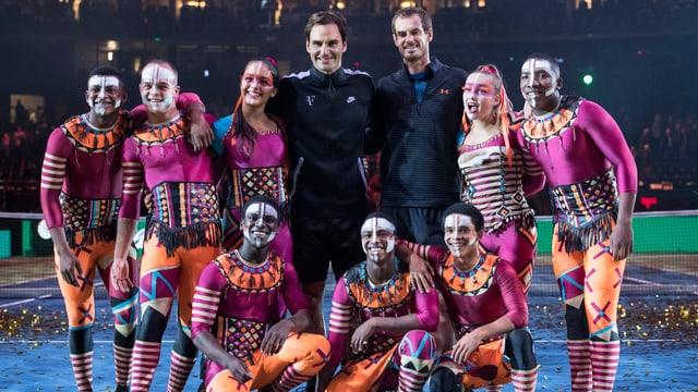 Gruppenfoto mit Roger Federer und Andy Murray und afrikanischen Tänzern, die farbenfroh angezogen sind und geschminkt.