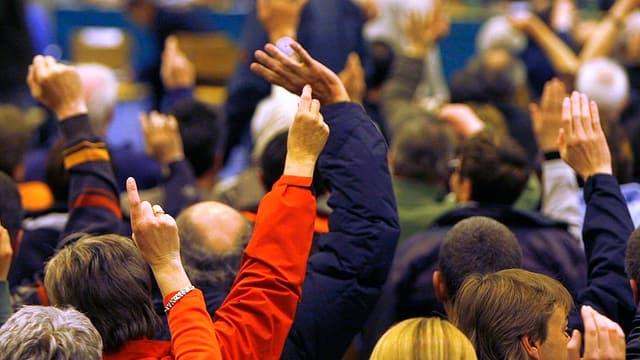 Leute erheben ihre Hand zur Abstimmung an einer Gemeindeversammlung