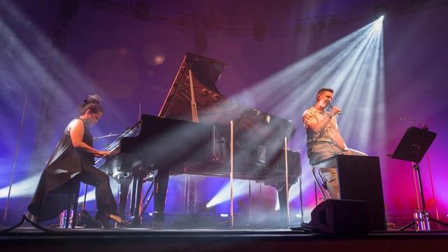 Ein Mann singt und eine Frau sitzt am Piano.