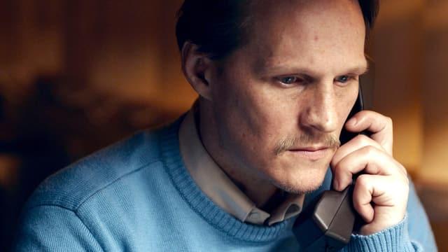 Nahaufnahme eines Mannes am Telefon, er schaut ernst und besorgt.