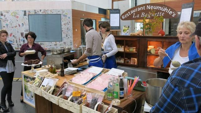 Frau schenkt an Marktstand Suppe aus