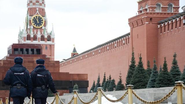 Zwei Polizisten laufen an der Mauer des Moskauer Kremls vorbei.