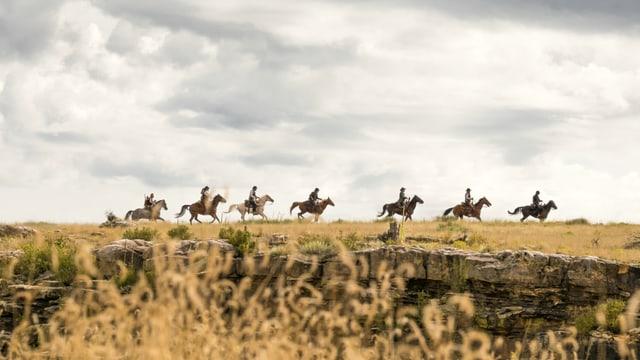 Die glorreichen Sieben reiten durch die Prärie.