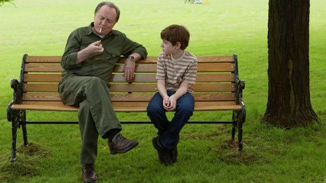 Ein kleiner Junge sitzt mit einem älteren Herren, der sich eine Zigarette anzündet, auf einer Parkbank.