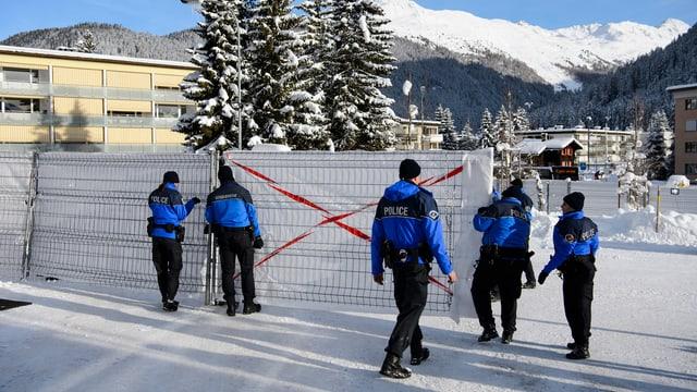 Polizisten stellen am WEF einen Zaun auf.