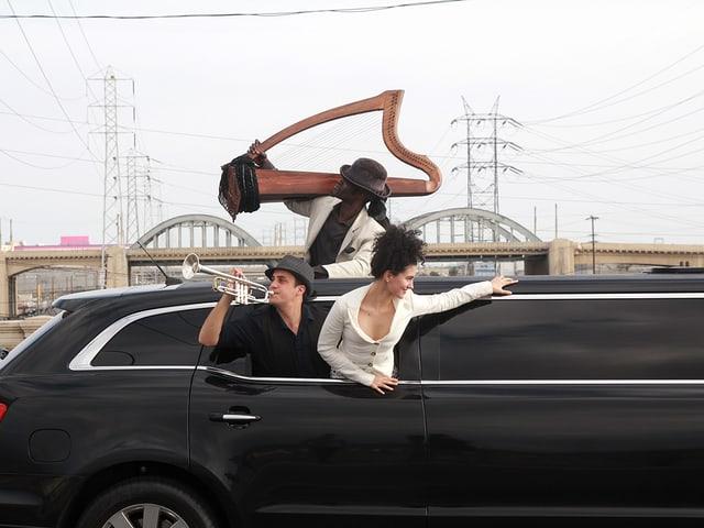 Oper on the road: Drei Musiker ragen aus dem Fenster einer fahrenden schwarzen Stretchlimousine.