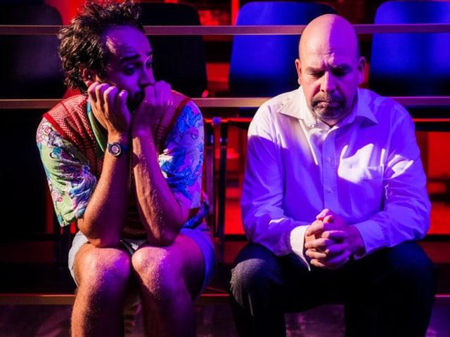 Zwei Männer sitzen am Bühnenrand und reden miteinander.