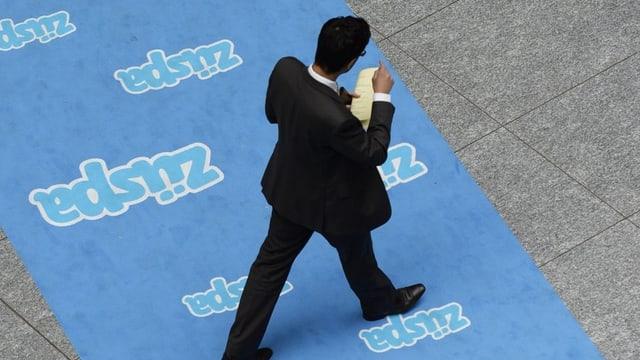 """Ein Mann in Anzug läuft über einen Teppich mit der Aufschrift """"Züspa"""", fotografiert von oben."""